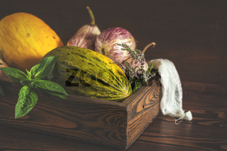 Melon, basil, mint, purple graffiti eggplants, onion and green fresh basil in a wooden box in a vintage wooden background in rustic style, selective focus, toned photo