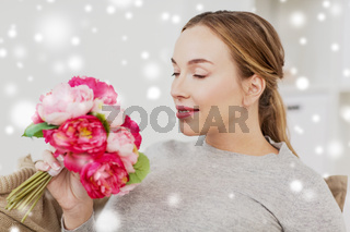 happy woman smelling flowers at home