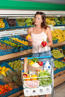 Grocery store shopping - Young woman choosing pepper
