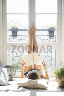 Young pretty girl reading fashion magazine near window