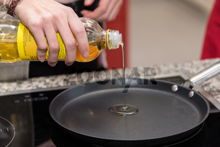 Öl wird in eine Bratpfanne gegossen - Nahaufnahme