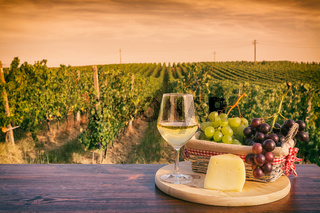 Glass of white wine in front of a vineyard at sunset
