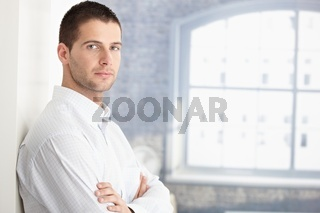 Handsome young man standing arms crossed