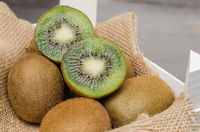 Box of fresh kiwi in on wooden background.