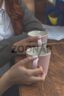 Two female teenagers drinking coffee at cafe restaurant with cup of espresso hot cappuccino on dating. Concept of female hands love and coffee. Italian delicious caffeine drink aroma latte