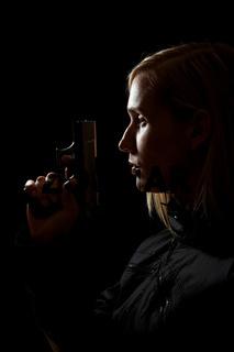 Frau hält Pistole im Dunkeln