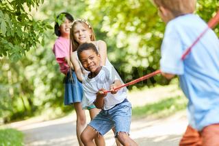 Gruppe Kinder als starkes Team beim Tauziehen