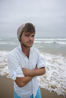 Young man at beach with beeny on head.