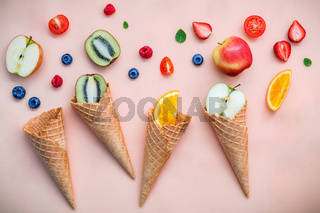 Cones and colorful various fruits raspberry ,blueberry ,strawberry ,orange slice , halve kiwi ,apple,tomato and peppermint leaves setup on pink background . Summer and Sweet menu concept flat lay.