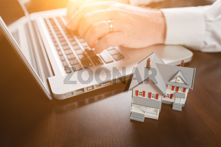 Miniature House Resting on Desktop And Man Using Laptop Computer.