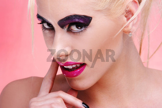 Young woman in pink portrait. violet make-up and big lips blonde funky hair style