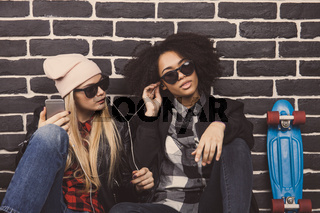 Lifestyle portrait of two hipster girls. They sit on the floor in front of a black brick wall and listen the music.