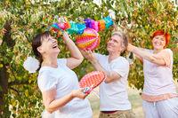 Senioren lachen beim dekorieren im Garten