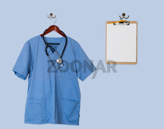 Blue scrubs shirt for medical professional hanging with clipboar