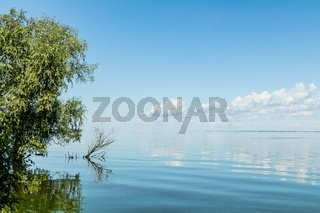 Blue sky with light white clouds over river surface