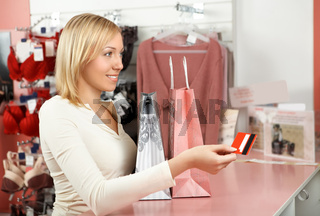 The blonde with packages in an underwear boutique holds a credit card in a hand
