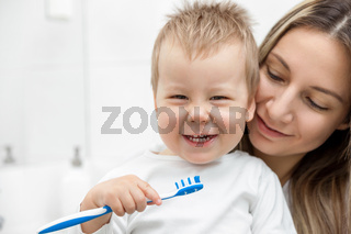 Happy mother teaching her son how to bush teeth in the bathroom