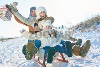 Familie beim Schlitten fahren mit Geschenken