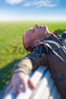 young man enjoying the sun on a white bench