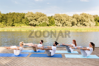 people making yoga in half-boat pose outdoors