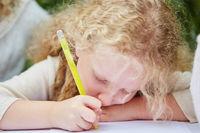 Kind malt und zeichnet mit einem Stift