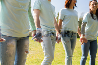 group of volunteers holding hands in park