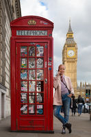 Woman talking on mobile phone, red telephone box and Big Ben. London, England