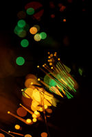 Abstract orange and green xmas lights using a defocused bokeh effect with a black background. The sparkling colored lighting is created from the blur of intense Christmas decorations.