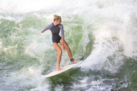 Atractive sporty girl surfing on famous artificial river wave in Englischer garten, Munich, Germany.