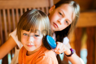 Pretty girl combing hair of younger sister