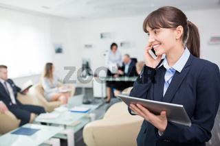 Junge Geschäftsfrau mit Tablet führt ein Telefonat