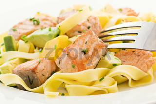 Wild salmon pieces with tagliatelle, mango and avocado as closeup on a white plate