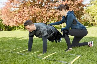 Frau trainiert Mann als Personal Trainer im Park