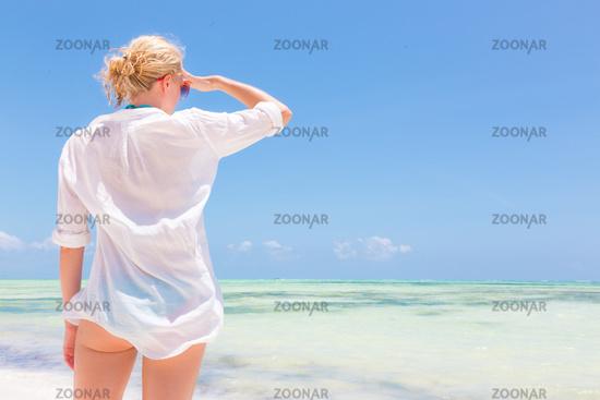 Happy woman enjoying, relaxing joyfully in summer on tropical beach.