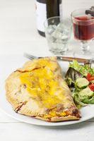 italienische Pizza Calzone auf einem Teller mit Salat