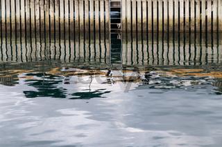 Spiegelung an einer Kaimauer in Andalsnes, Norwegen