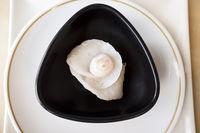 Rose flower shaped cod Sashimi Sushi over black bowl
