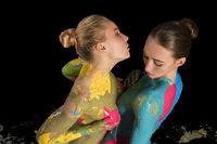Two nude girls with colorful bodyart cropped shot