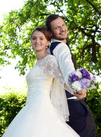 Happy fresh married couple with bridal bouquet