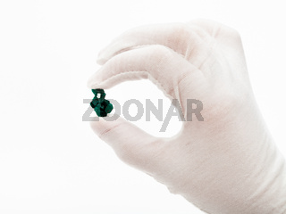 master in white glove holds dioptase crystal