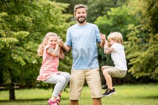 Kinder toben mit dem Vater herum