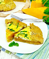Pie of pumpkin and basil in plate on board