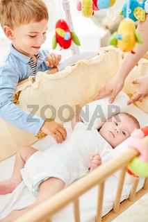 Lächelnder Junge schaut auf neugeborenes Baby