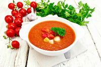 Soup tomato in white bowl with vegetables on napkin