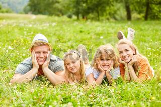 Glückliche Eltern und Kinder im Garten im Gras
