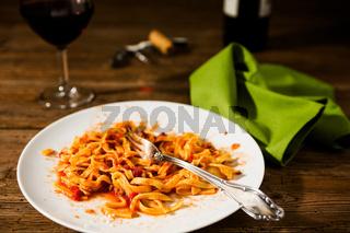 Half-eaten tagliatelle pasta with bolognese ragu and red wine