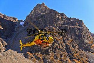 Hubschrauber Eurocopterim Einsatz im Val Lischana in den Engadiner Alpen, Schweiz