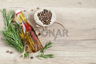 Rosemary bunch of bouquets, olive oil with pepper and spices, fragrant pepper on light wooden surface. Top view, copy space.