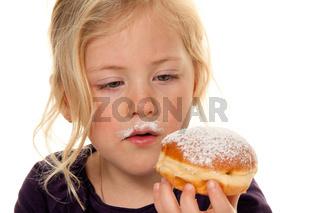 Kind im Fasching mit Krapfen. Faschingskrapfen