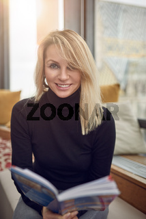 Smiling woman holding book while sitting down